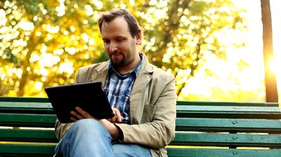 stock-footage-young-happy-man-with-tablet-computer-sitting-in-the-park